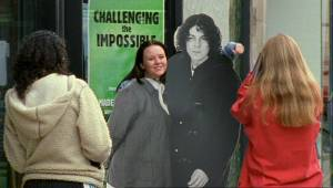 Maddy sees the teenagers posing for photos with Jonathan Creek - they have removed Maddy's head from the life-sized cardboard cuts outside the book store