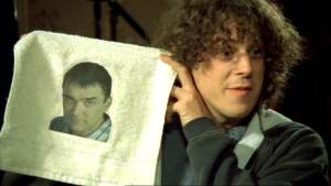 Jonathan holds up his present from Adam - a face flannel with Adam's face on it.